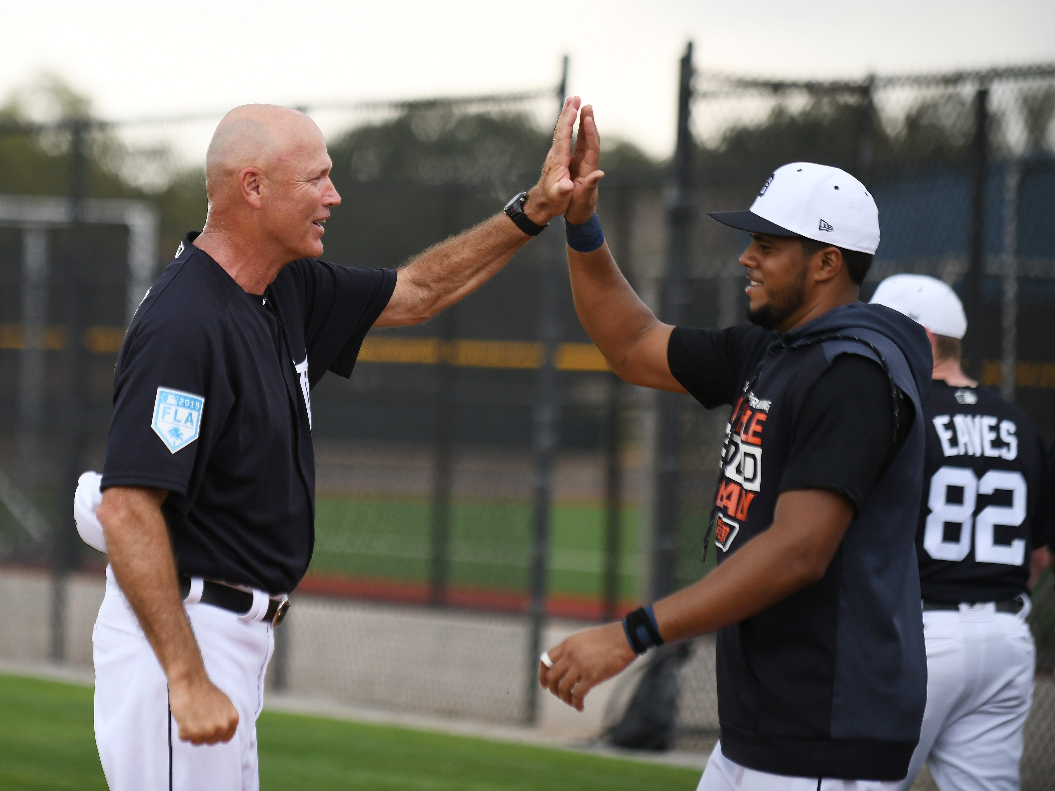 Tigers bench coach Steve Liddle, left, high fives Jeimer Candelario near the end of the first full squad workout.