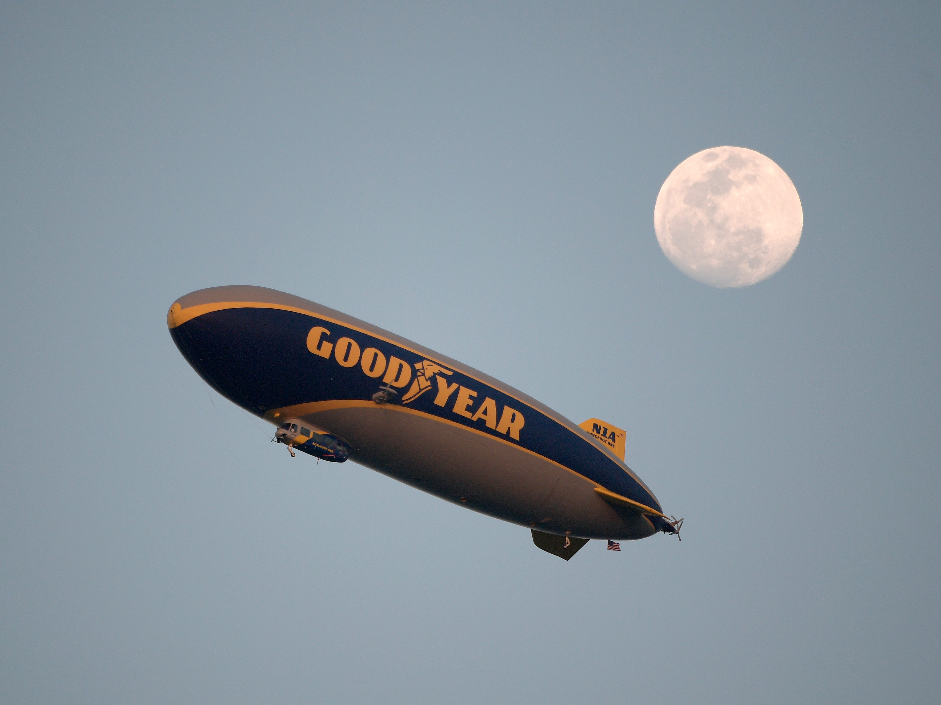 The Goodyear blimp flies in view of the moon during the NASCAR Daytona 500 auto race at Daytona International Speedway.