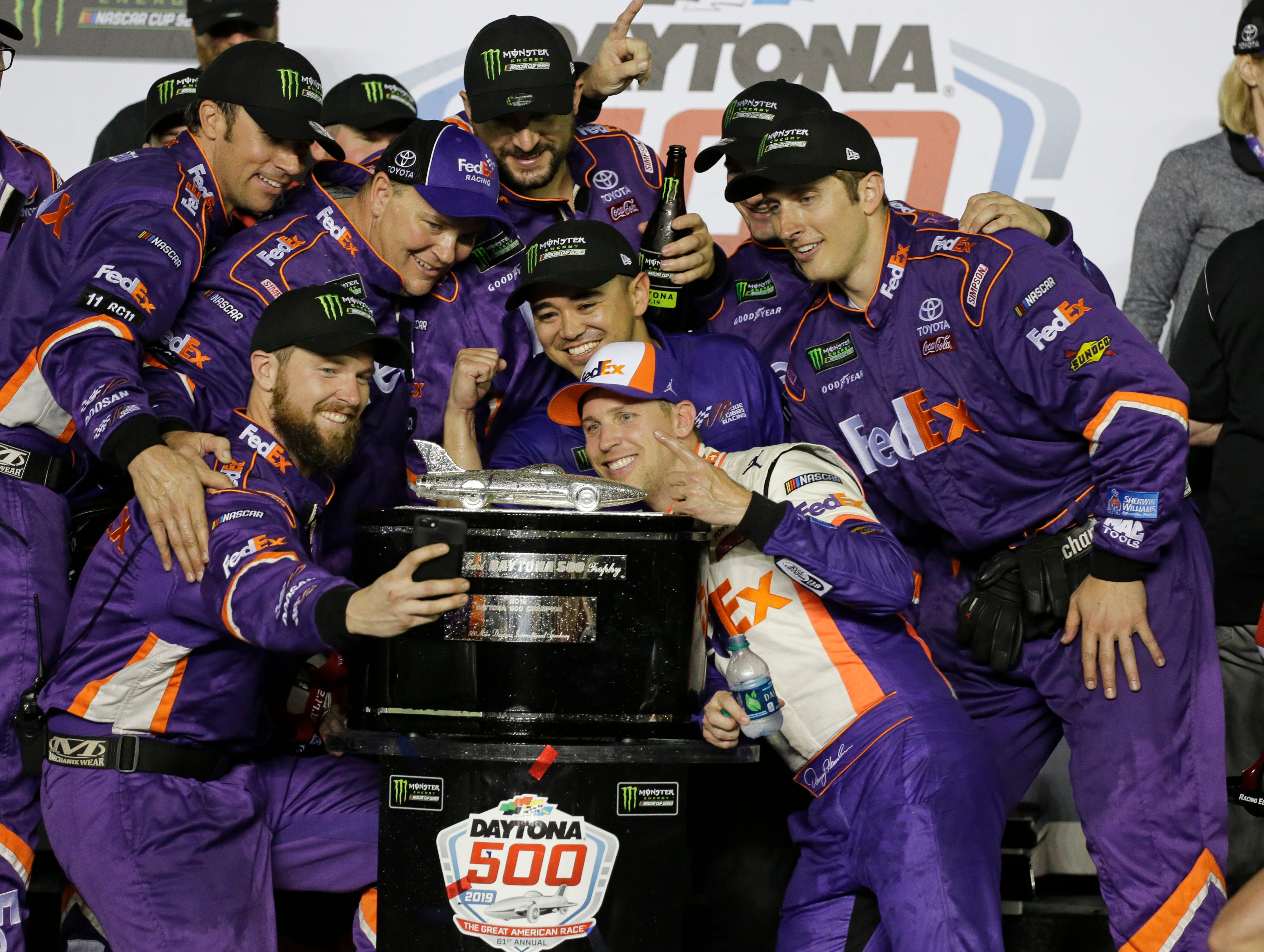 Denny Hamlin, center front, poses for a photo with his crew members after winning the NASCAR Daytona 500 auto race at Daytona International Speedway, Sunday, Feb. 17, 2019, in Daytona Beach, Fla.