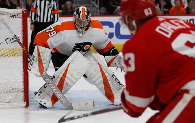 Red Wings defenseman Trevor Daley (83) shoots toward Flyers goaltender Carter Hart (79) during the second period Sunday in Detroit.