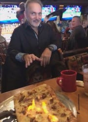 Owner Louie Bricolas with the flaming saganaki pizza at Gilbert's Lodge.