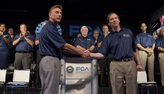UAW Vice President Norwood Jewell, left, and Fiat Chrysler Vice President Glenn Shagena shake hands during the ceremonial start of contract negotiations in 2015.