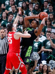 Michigan State's Nick Ward is pressured by Ohio State's Kyle Young during the first half Sunday.