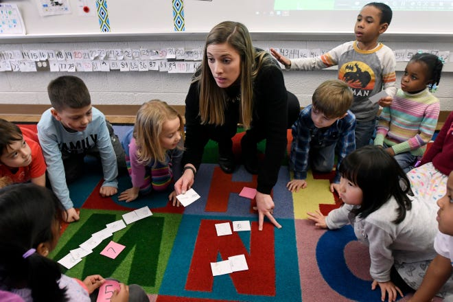 Gill Elementary kindergarten teacher Jordan Holmes and her students compile data to make a bar graph of the number and type of pets owned by them in their class, Monday, Feb. 11, 2019 in Farmington Hills, Mich.