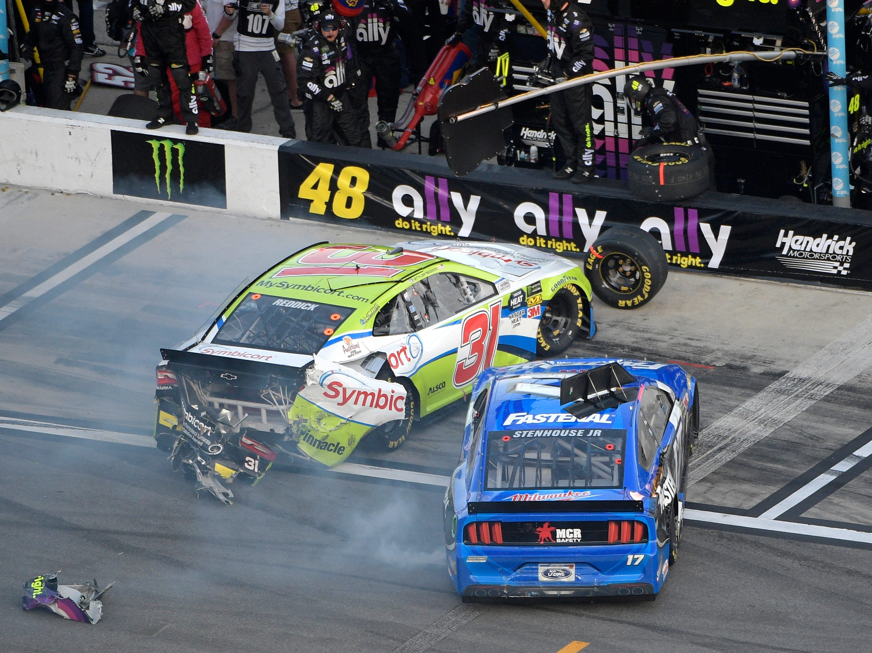 Tyler Reddick (31) and Ricky Stenhouse Jr. (17) slide into a pit stall after colliding during a NASCAR Daytona 500 auto race at Daytona International Speedway.