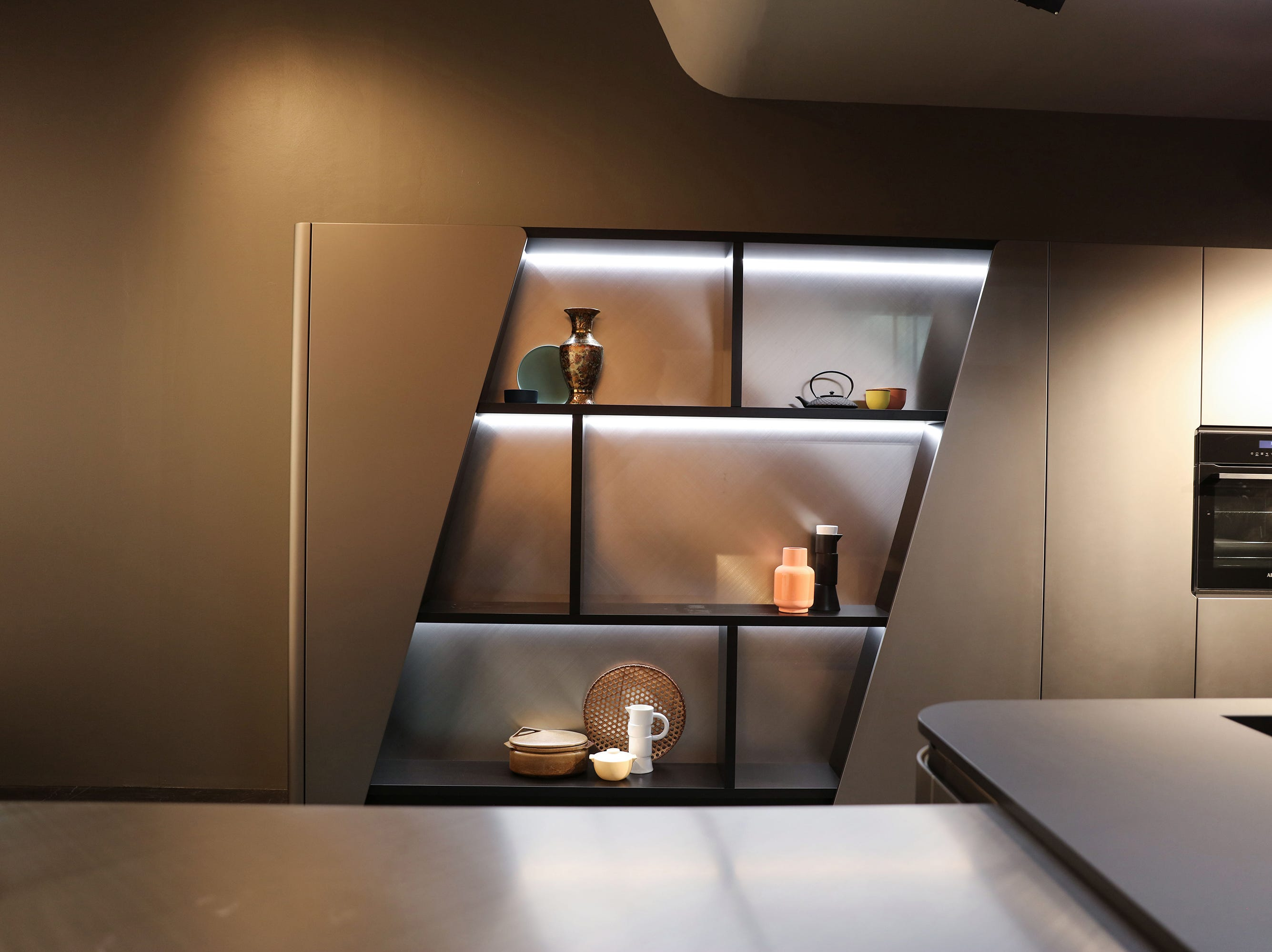 The illusion of shelves with angled sides was created by the side panels at Snaidero. But the shelving itself has a modern look, with its supersizing, stainless back and LED lighting.