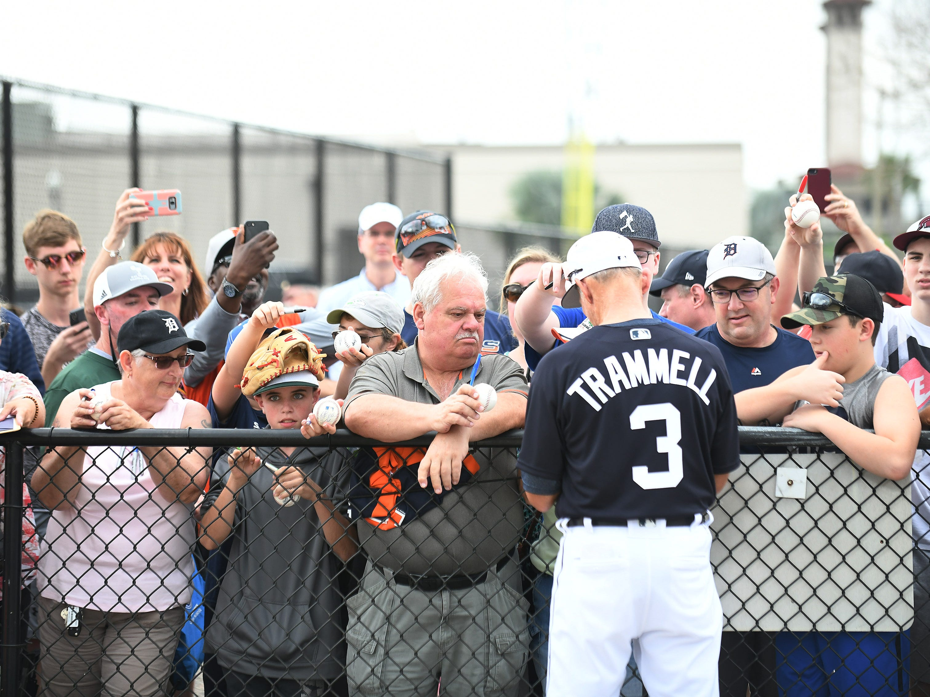 Hall of Famer Alan Trammell signs for fans at the first full squad workout.