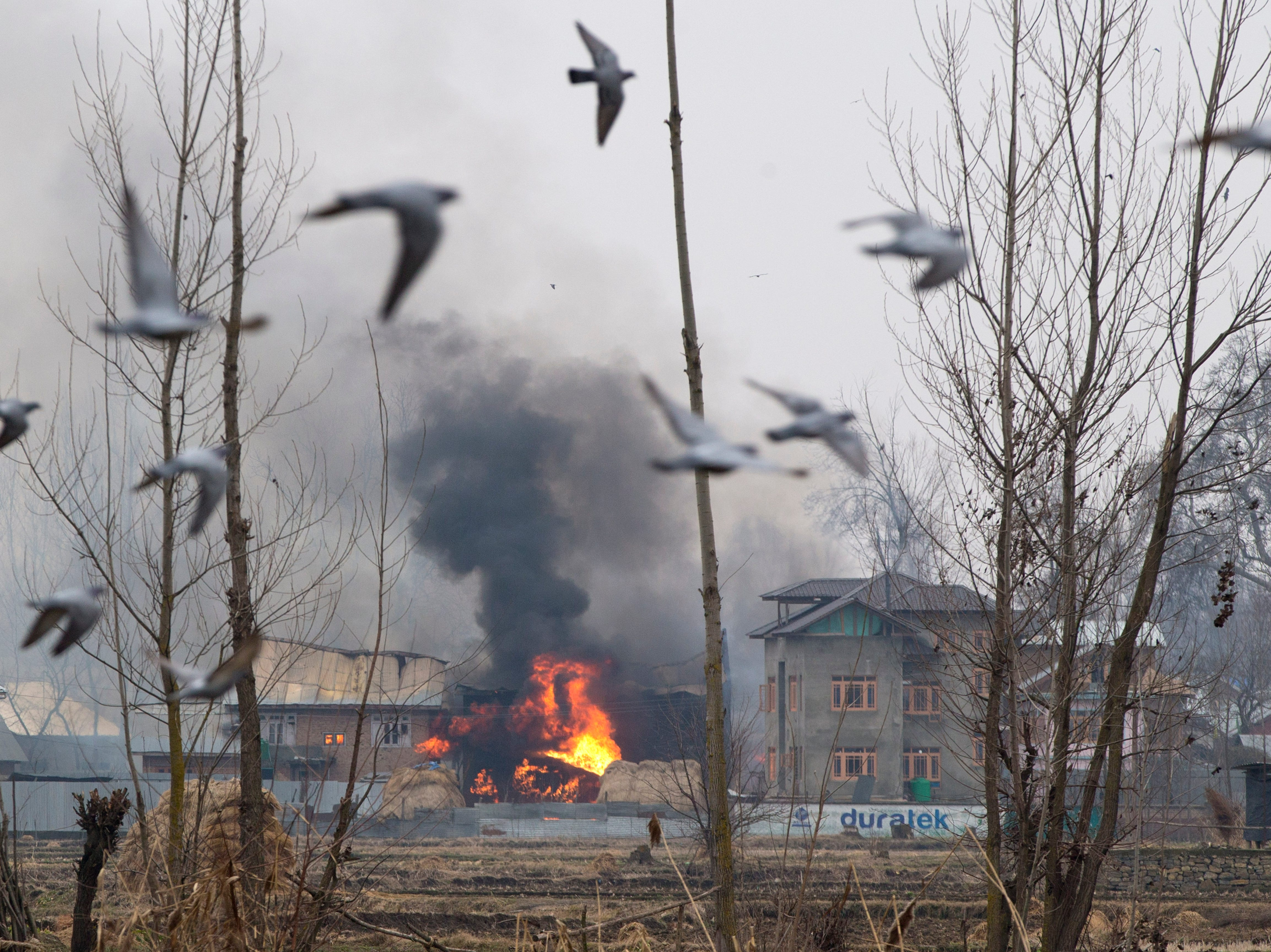 Flames and smoke billows from a residential building where militants are suspected to have taken refuge during a gun battle in Pulwama, south of Srinagar, Indian controlled Kashmir, Monday, Feb. 18, 2019. Tensions continued to rise in the aftermath of a suicide attack in disputed Kashmir, with seven people killed Monday in a gunbattle that broke out as Indian soldiers scoured the area for militants.