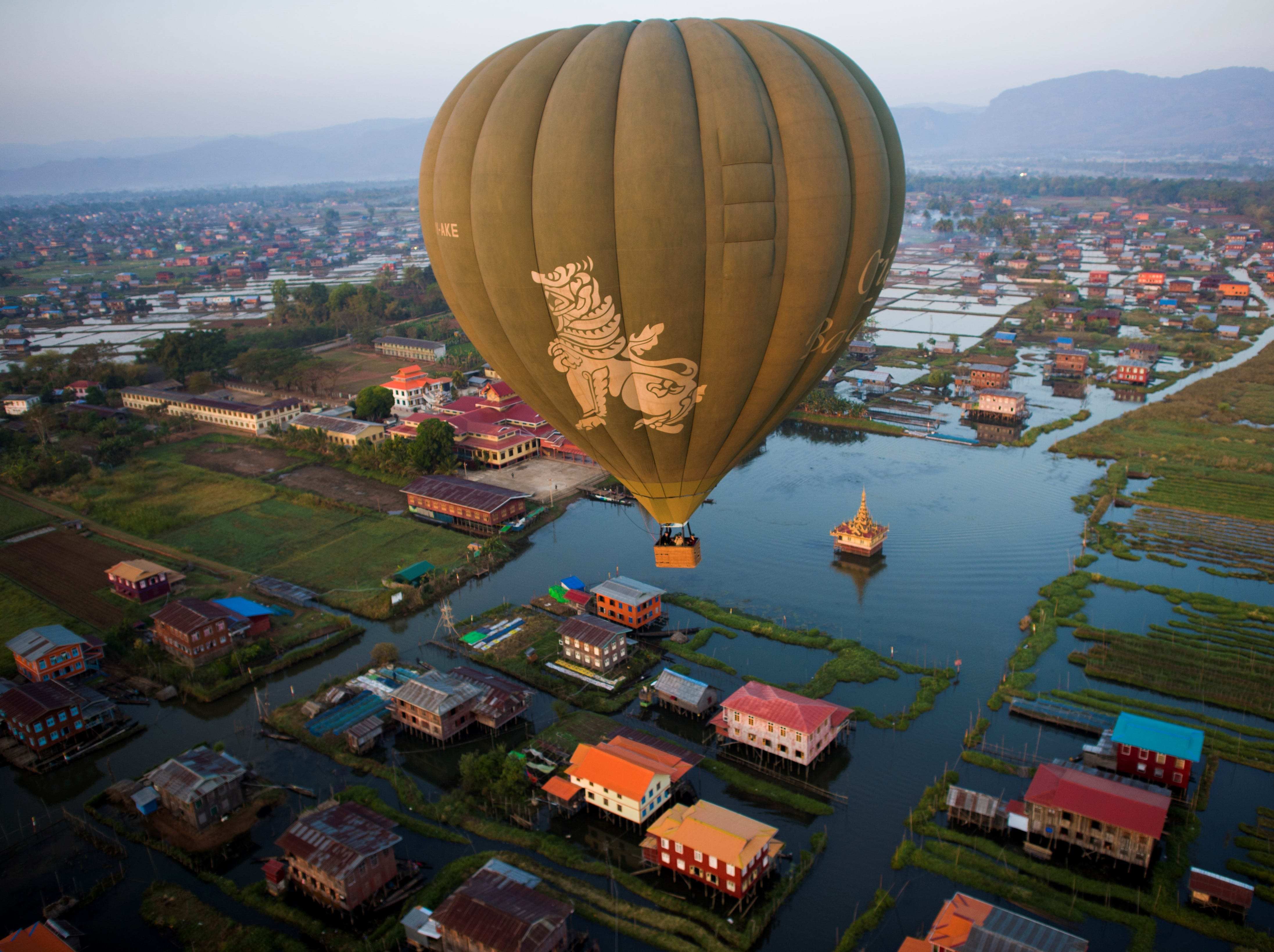 This aerial photo shows a hot-air balloon flying over traditional houses on stilts on Inle lake in Shan State on Feb. 18, 2019.