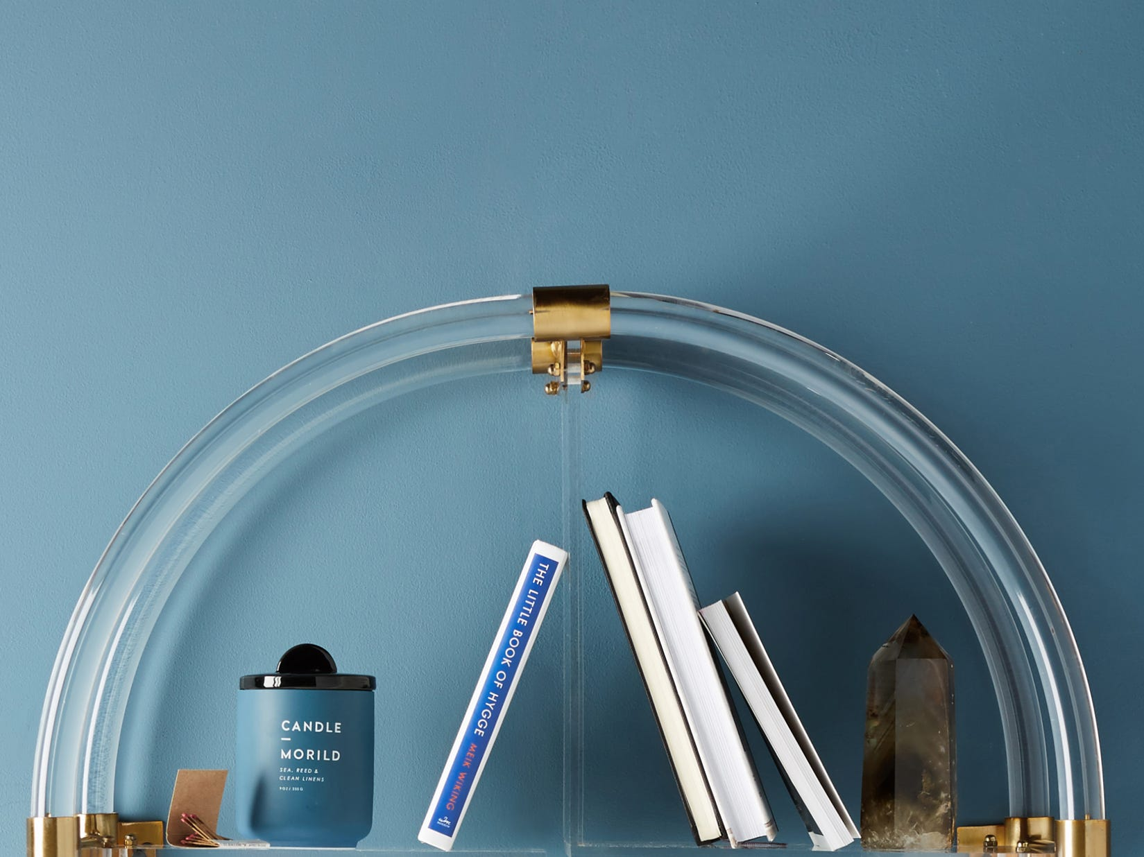 Hanging shelving with style: This light-catching Lucite arch with brass supports that also are decorative from Anthropologie is the perfect platform for showcasing prized possessions. It is 26 inches tall, 24 3/4 inches wide and 10 1/2 inches deep.