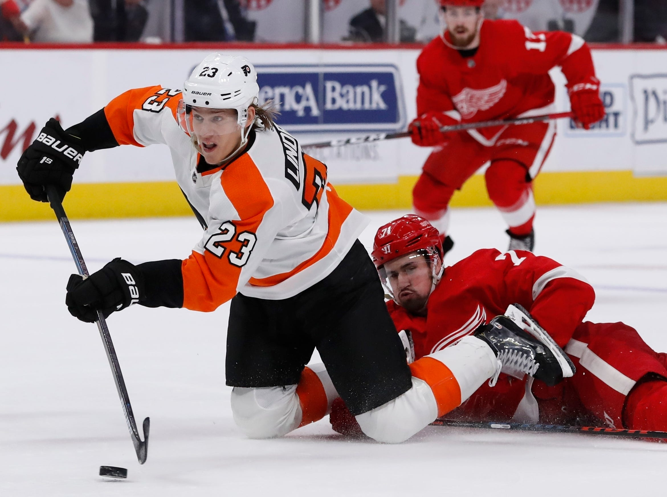 Philadelphia Flyers left wing Oskar Lindblom (23) falls in front of Detroit Red Wings center Dylan Larkin (71) and shoots an empty net goal during the third period.