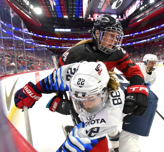 U.S's Kacey Bellamy (22) and Canada's Natalie Spooner (24) mix it up in the corner near the end of the second period.
