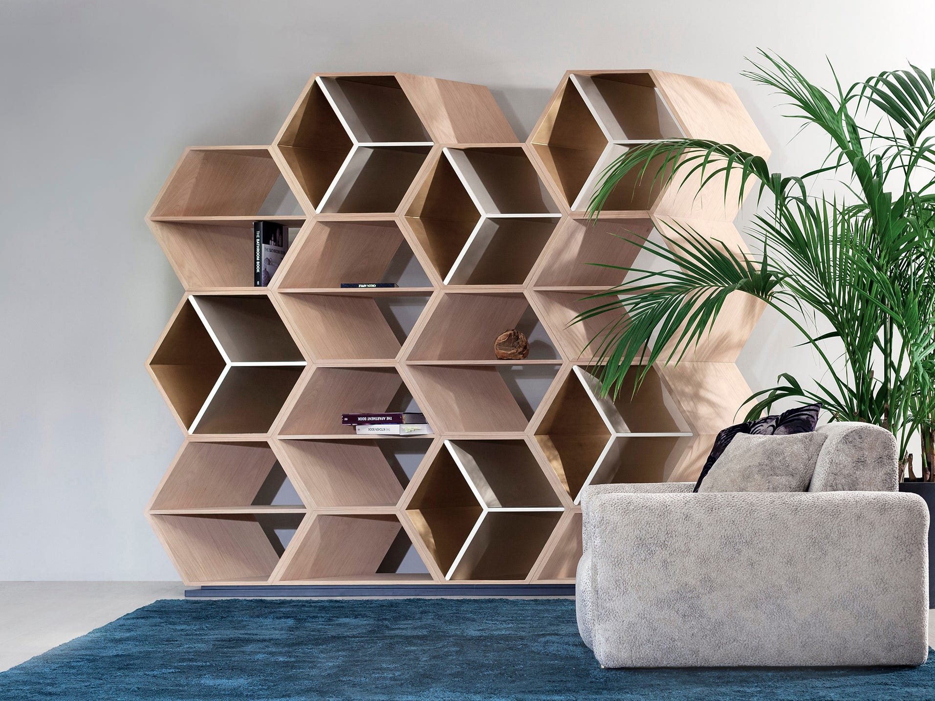 Hexagonal box shapes take on a new dimension, laid up on a diagonal, creating a wooden beehive-like solution to storage from Green Apple. The natural American oak wooden bookcase is lacquered in high-gloss cream, strategically punctuated with details in high-gloss bronze powder champagne and semi-gloss oxidized gold applied by hand. The barely there base is lacquered in semi-gloss black. The bookcase is 105.1 inches wide, 91.7 inches tall and 15.7 inches deep.