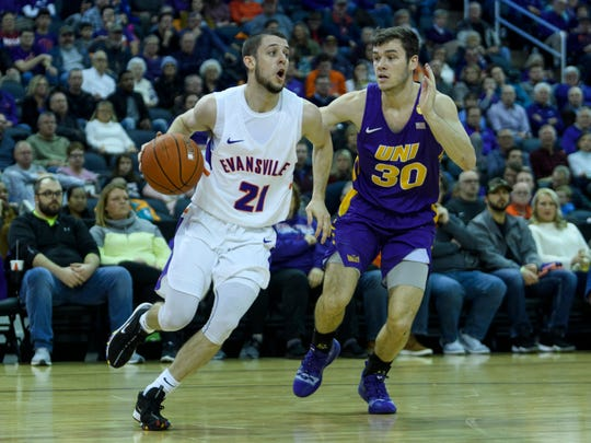University of Evansville's Shea Feehan (21) drives past University of Northern Iowa's Spencer Haldeman (30) in the first half at Ford Center in Evansville, Ind., Sunday, Feb. 17, 2019. The Purple Aces fell 73-58 to the University of Northern Iowa Panthers.