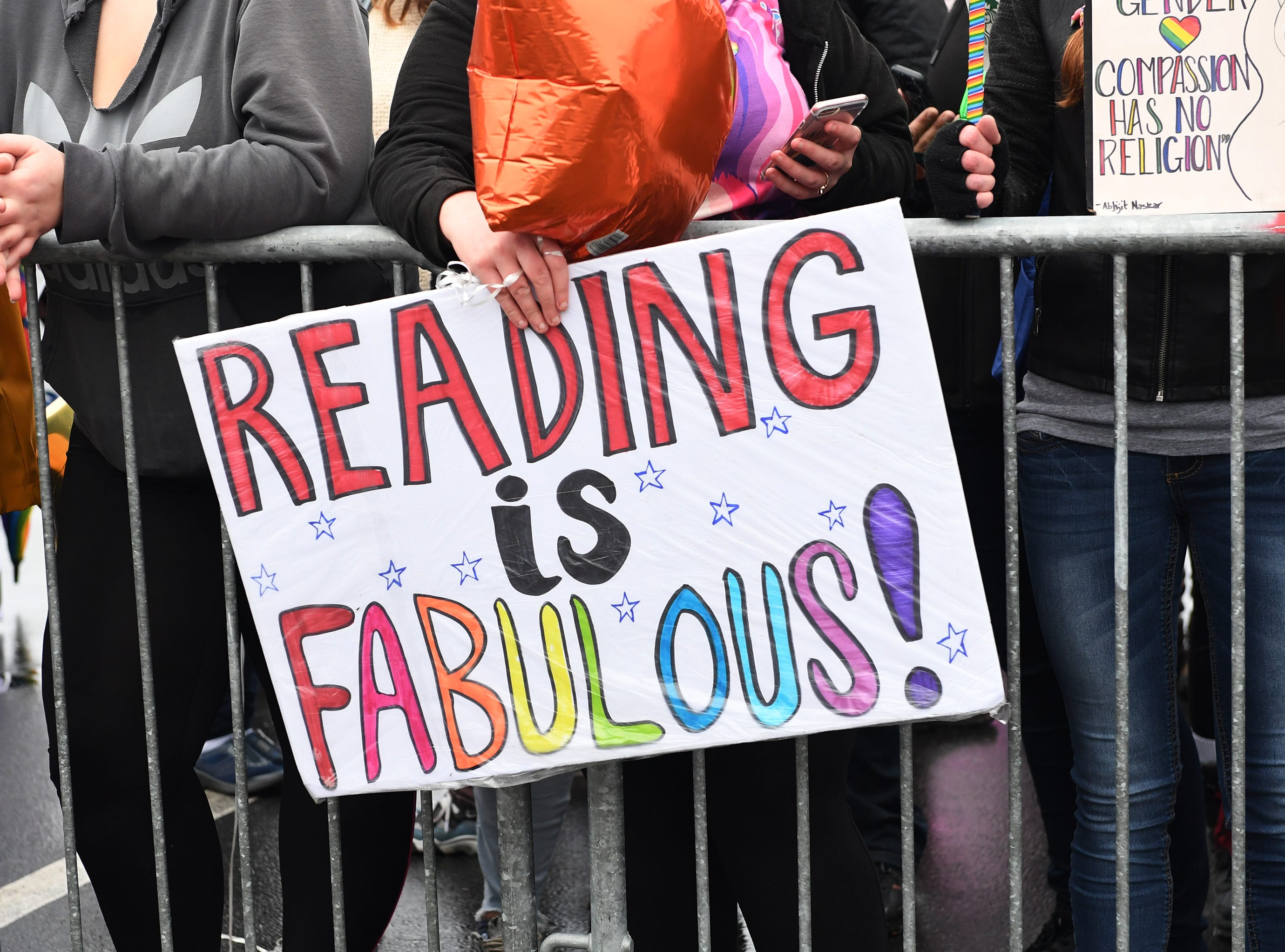 People gathered in support of Drag Queen Story Hour hold signs outside Five Forks Branch Library Sunday, Feb. 17, 2019.