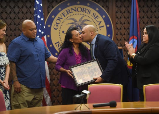 Acting Gov. Josh Tenorio presents the Ancient Order of Chamorri Award to Mahina Anderson, the wife of the late Jon A. Anderson, and their family at the Ricardo Bordallo Governor's Complex on Feb. 18, 2019.