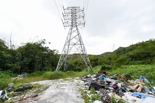 Trash is illegally dumped at the end of a roadway near a high tension tower in Agana Heights, Feb. 18, 2019.