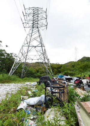 Trash is illegally dumped at the end of a roadway near a high tension tower in Agana Heights.