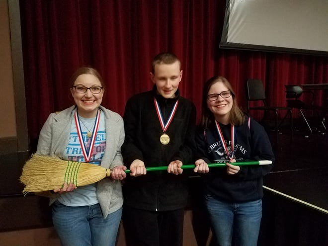 Henderson County High School freshmen Abby Salisbury, Josh Freeman and Julianne Latimer pose with a broom they adopted as a lucky charm during the Region 3 Governor's Cup academic team meet at Owensboro High School Saturday. Salisbury placed fourth in Language Arts, Freeman was fifth in Science and Latimer was fifth in Mathematics. Henderson County finished second overall to Daviess County but qualified its quick recall team and in 12 individual areas of written assessment for March's state tournament.