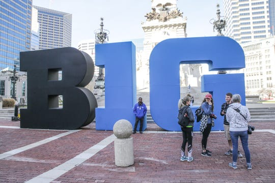 Adjunct Instructor at Herron School of Art + Design, Mary McClung, far right, and her photo one students visit the Big Ten women's basketball tournament sign on Monument Circle in Indianapolis on Tuesday, Feb. 27, 2018.