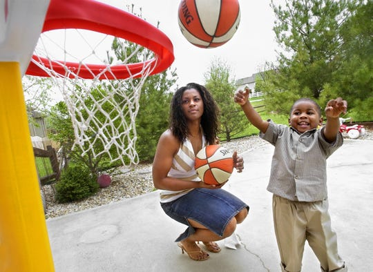 In this 2004 file photo, former Indiana Fever player Niele Ivey plays basketball with her 2-year-old son Jaden in their backyard.