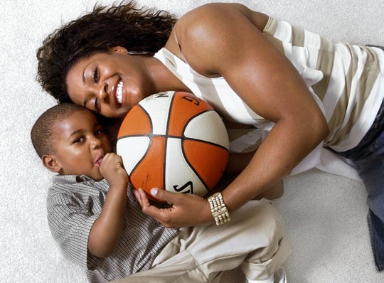 In this 2004 file photo, Indiana Fever player Niele Ivey cuddles with her 2-year-old son Jaden in their Indianapolis home.
