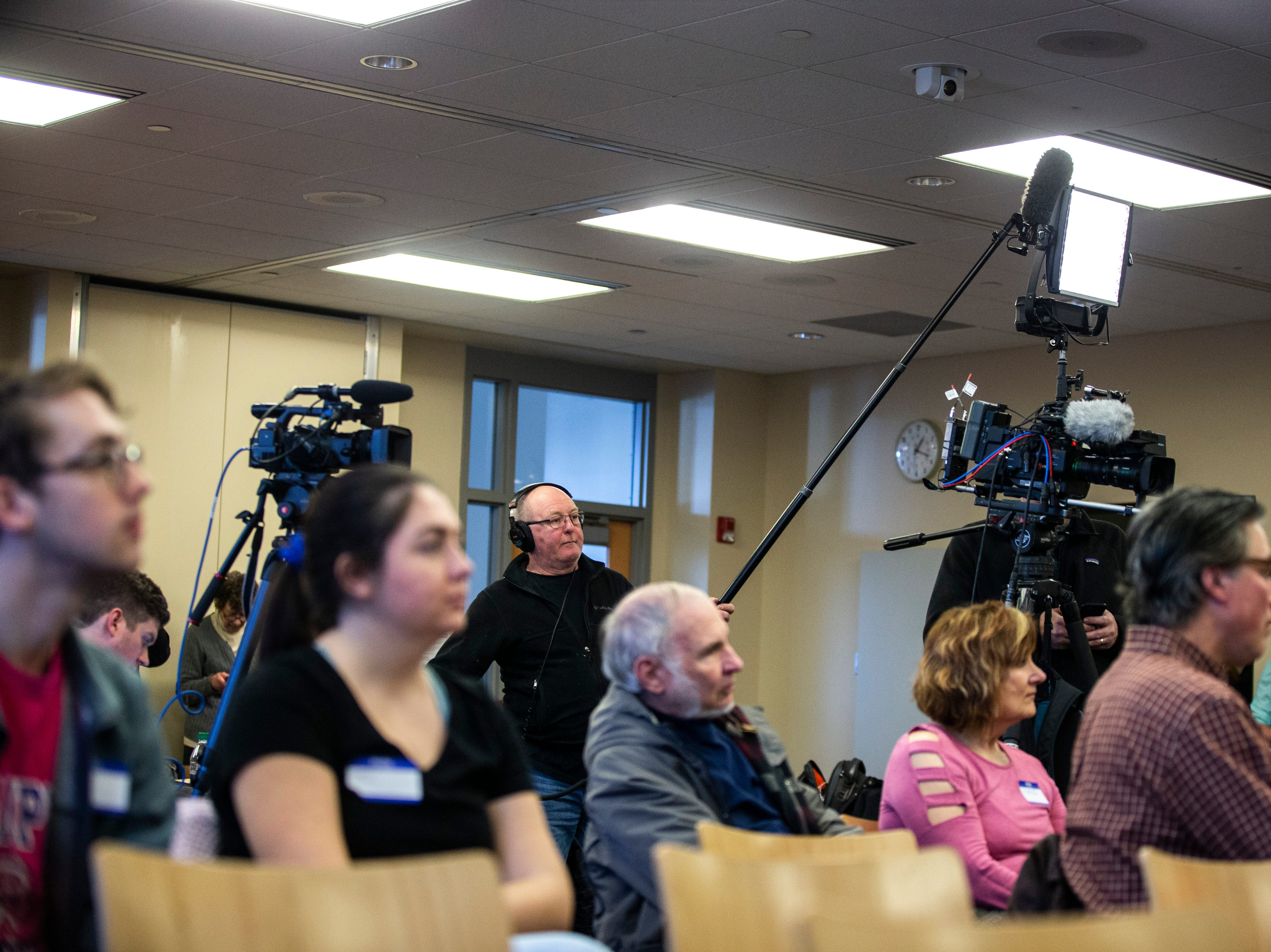 Television crews work during a Working Hero Iowa event on Monday, Feb. 18, 2019 at the Public Library in Iowa City, Iowa.