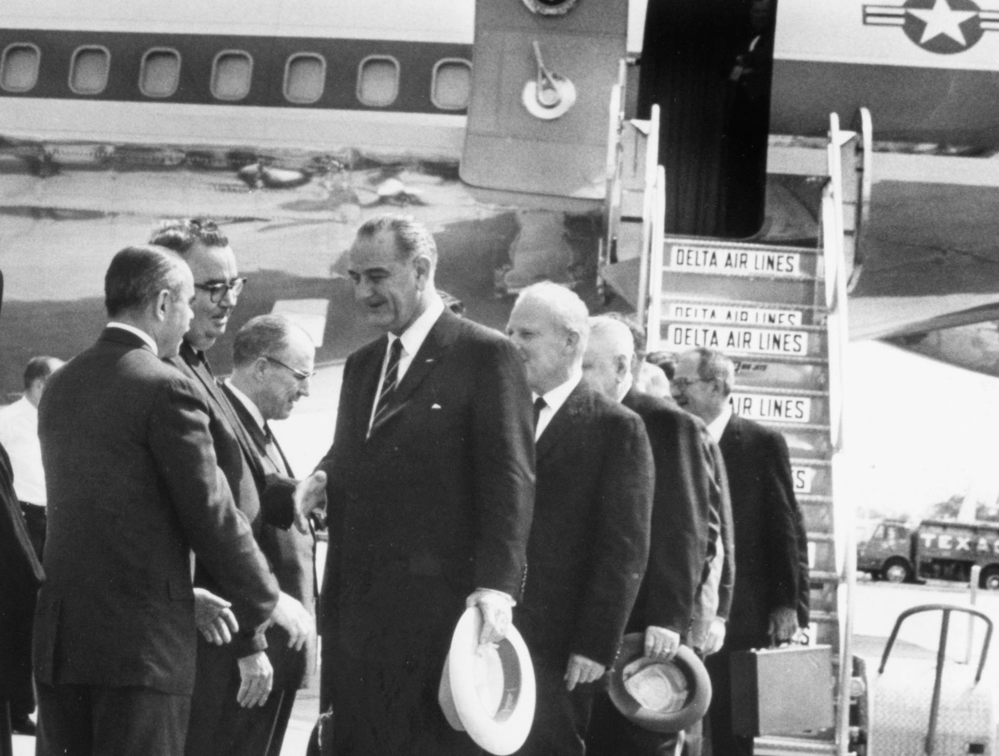 In a May 8, 1964 photograph, President Lyndon B. Johnson arrives at Municipal Airport. Among those pictured are Sam Sapirie of the Atomic Energy Commission, TVA Director Frank Smith, TVA Director A.R. Jones, and U.S. Sen. Albert Gore Sr.