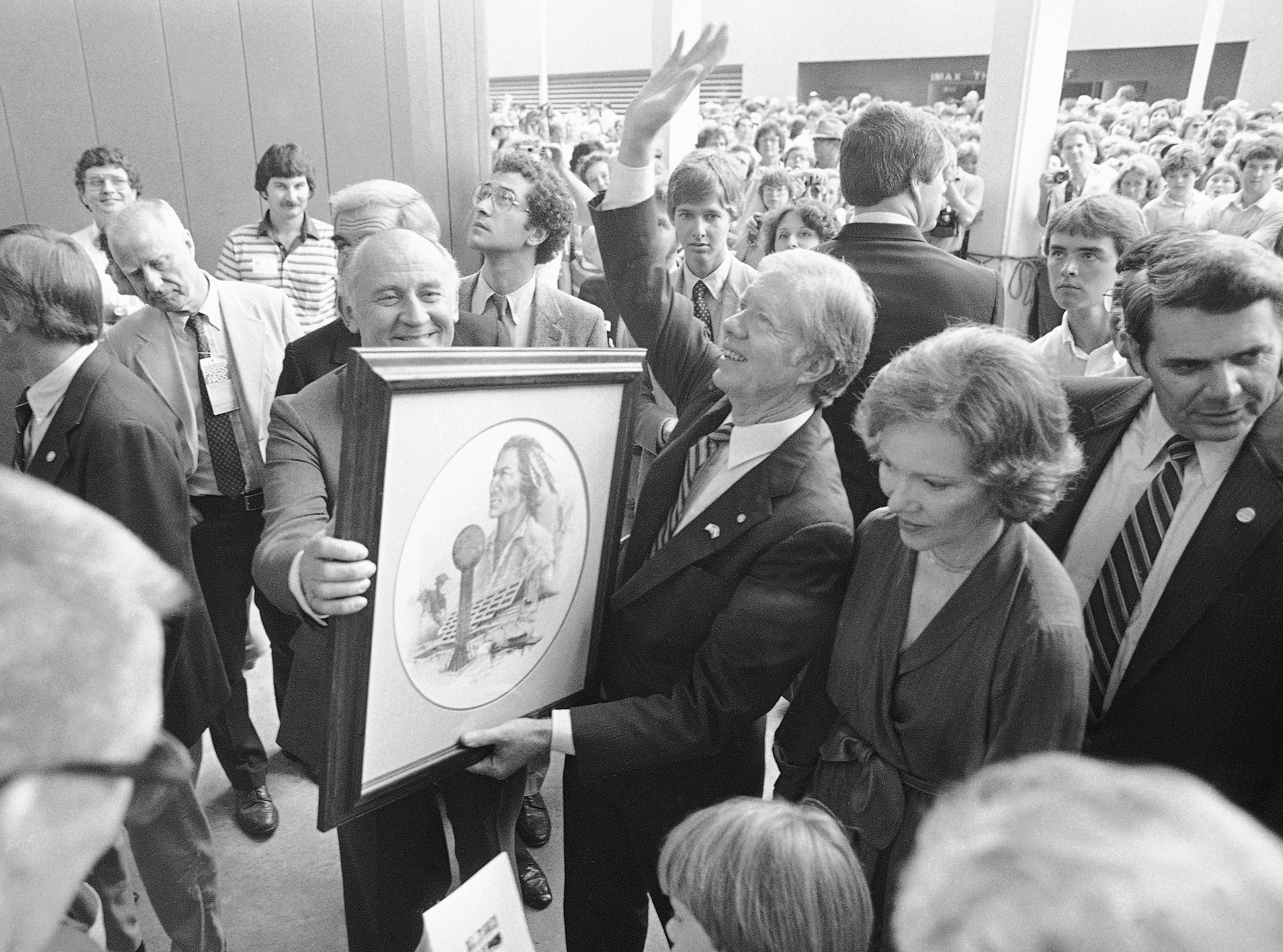 Former President Jimmy Carter, with his wife, Rosalynn, waves to the crowd as he receives a painting as a gift at the World's Fair on Oct. 11, 1982.