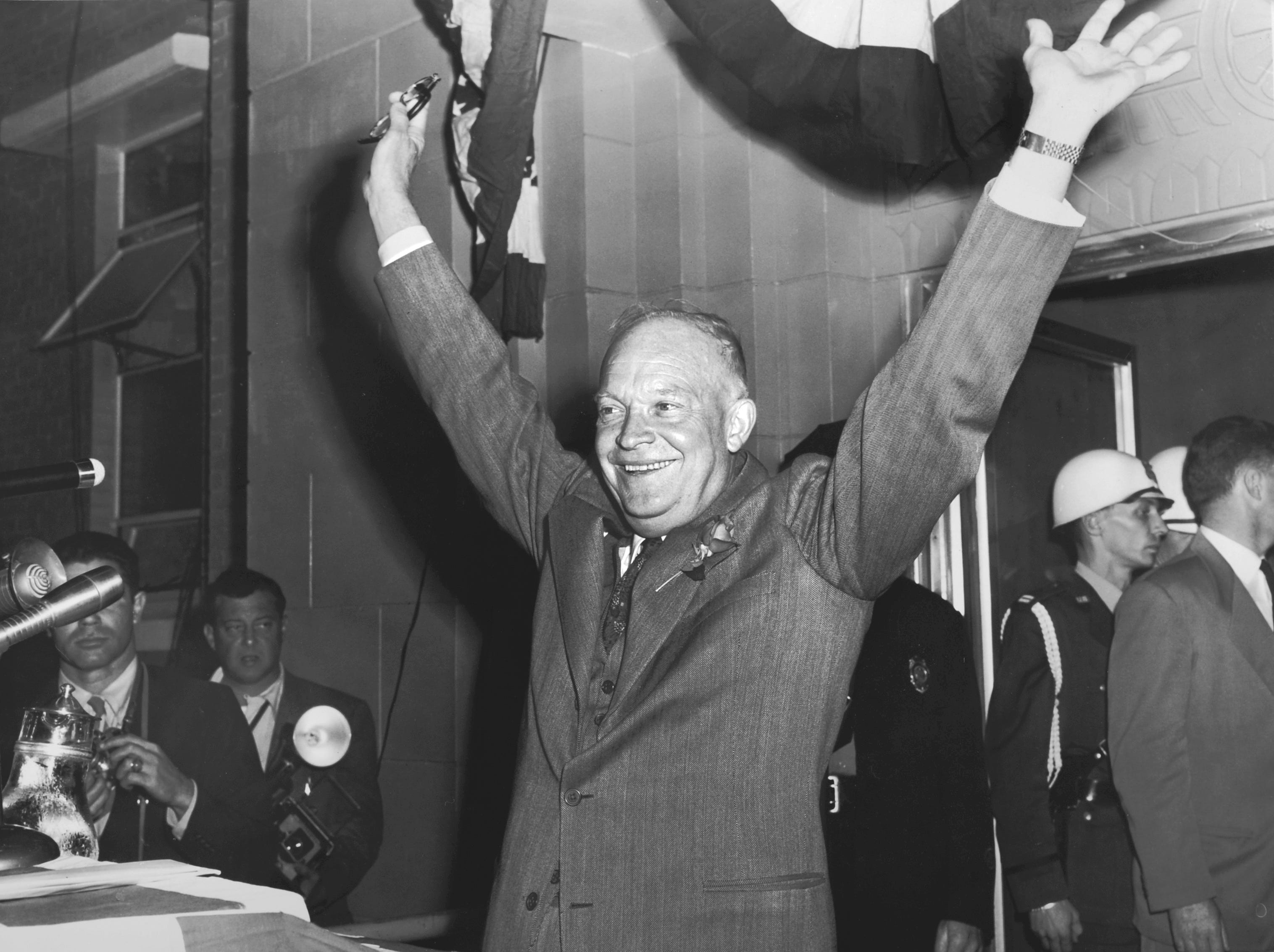 """Republican Presidential nominee Gen. Dwight D. Eisenhower waves to the crowd during an Oct. 15, 1952 campaign appearance at Knoxville's Municipal Airport. The News Sentinel account noted that Ike sported a red rose on his lapel and  """"appeared to be wearing some kind of make-up, possibly for the benefit of motion picture and television cameras."""""""