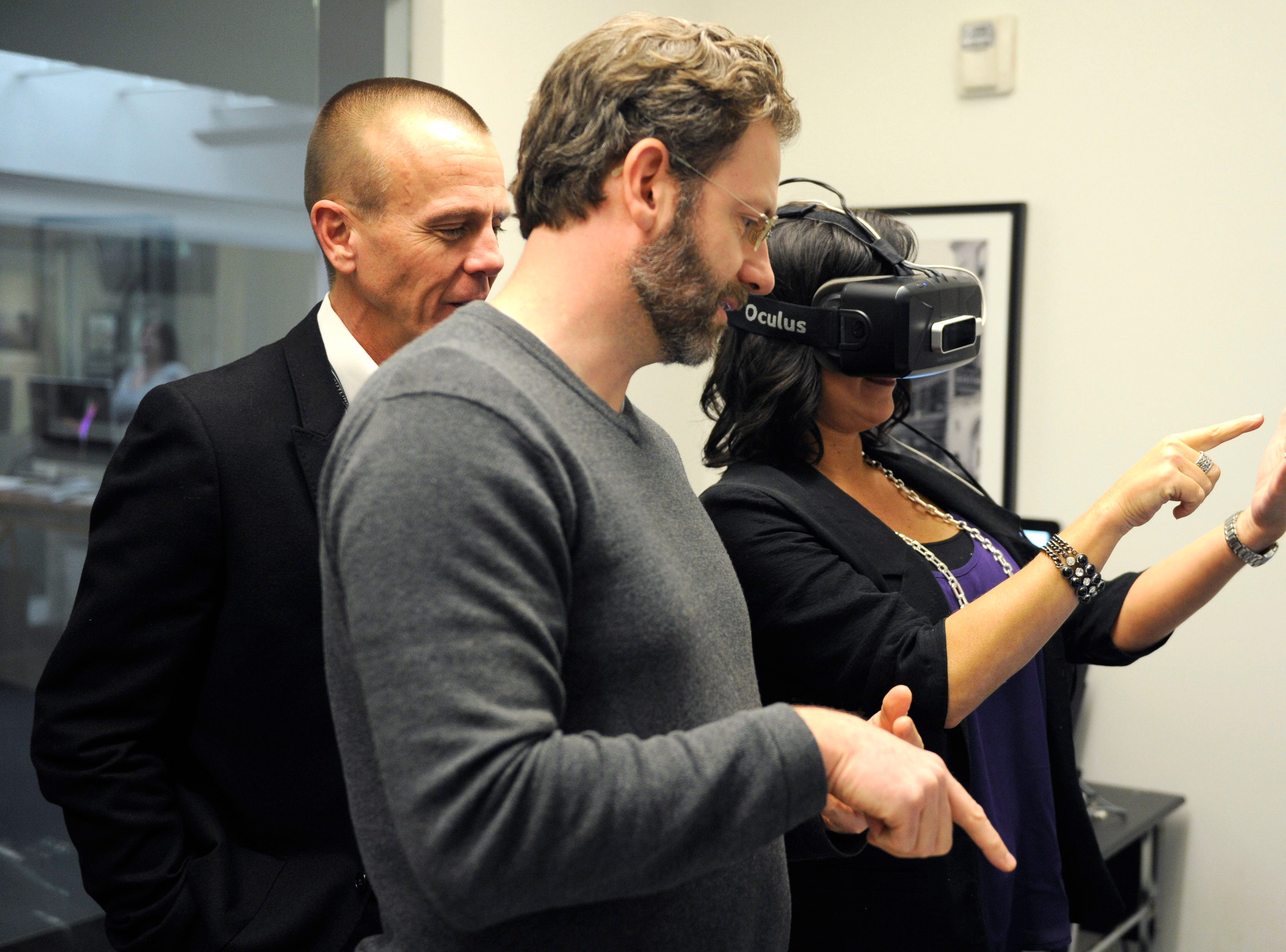 The Tombras Group senior vice president David Avery, left, and creative technologist Andre Hayter, center, assist executive assistant Krista Stevenson in using the companies newly developed Virtual Reality Lab using Oculus Rift, Monday, Feb. 8, 2016.