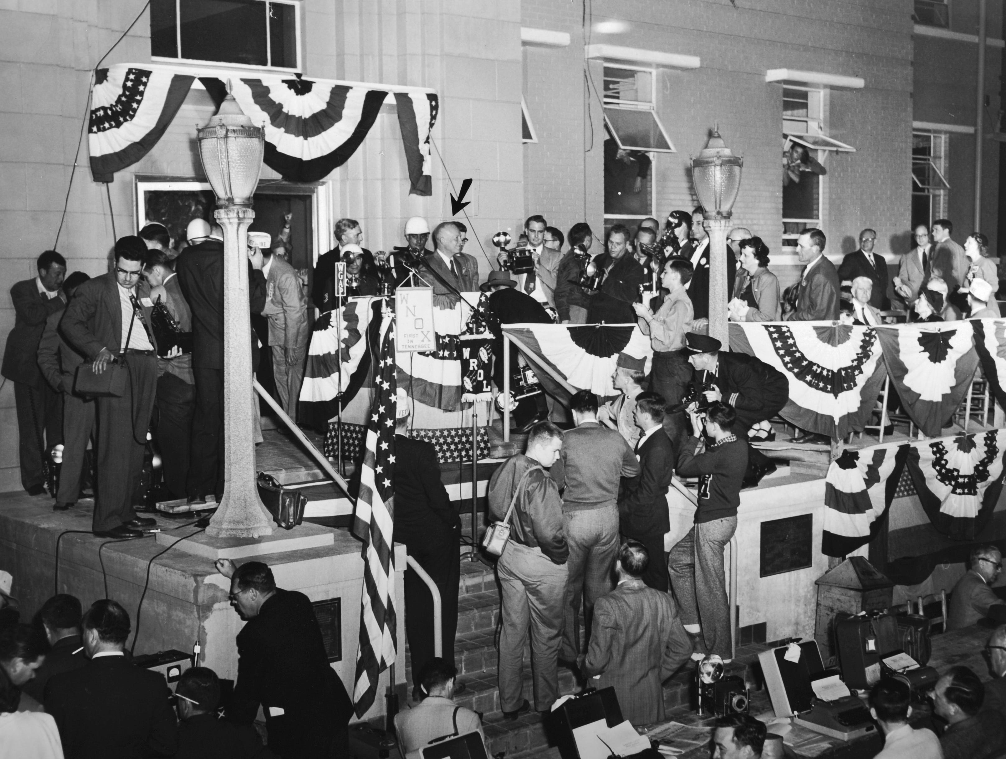 """An arrow points out Republican Presidential nominee Gen. Dwight D. Eisenhower during an Oct. 15, 1952 campaign appearance at Knoxville's Municipal Airport. In his speech, Ike assured the crowd there was """"no disposition on my part to impair the effective working out of TVA.""""  News Sentinel Editor Loye Smith was among the dignitaries on the dais."""