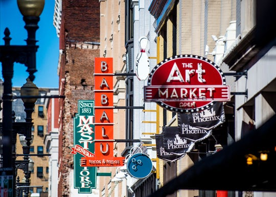 Signs of businesses along Gay St. in downtown Knoxville.