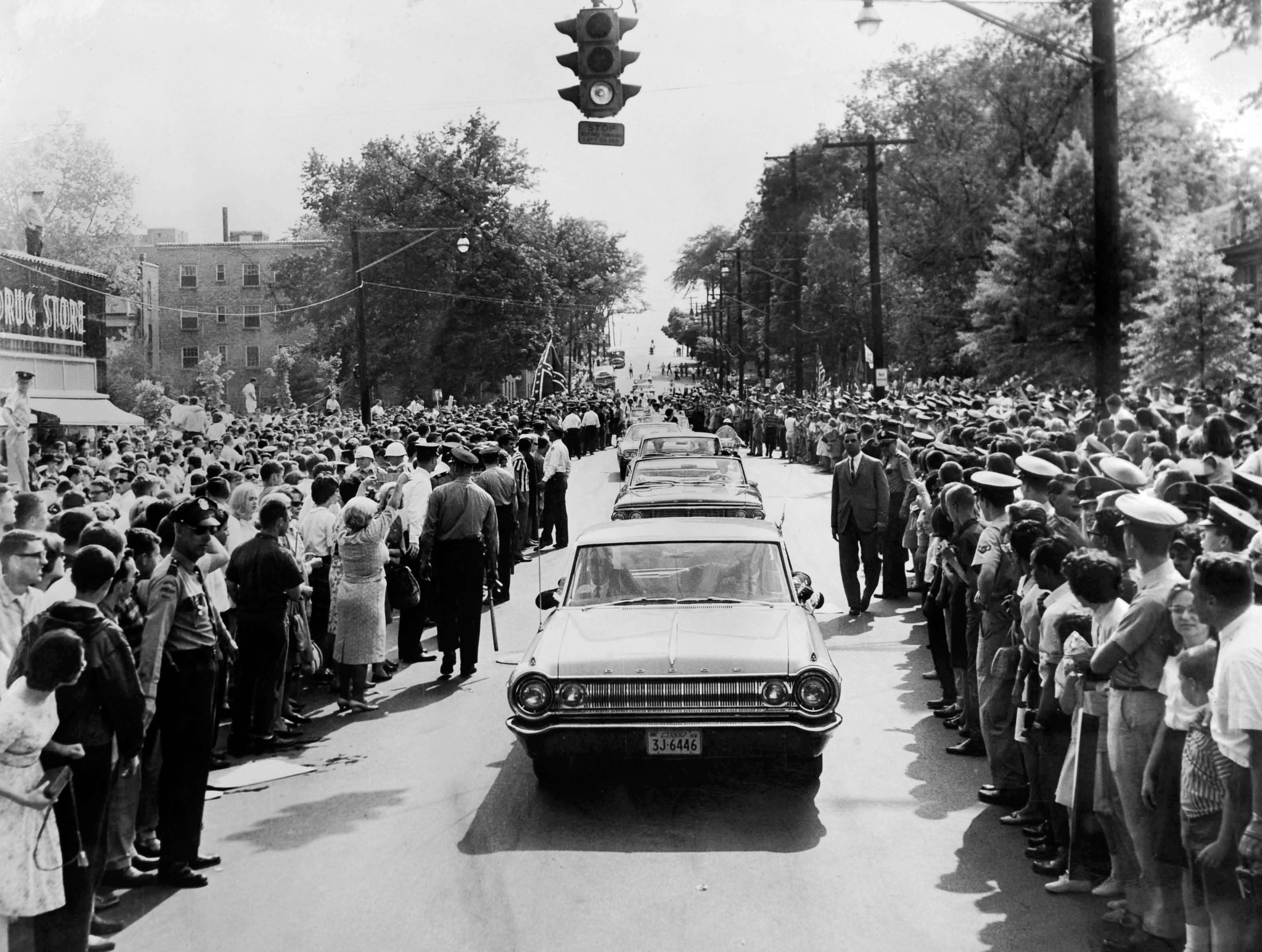 """In a May 7, 1964 photograph, President Lyndon B. Johnson's motorcade moves among a vast crowd in front of Ellis & Ernest Drugstore on Cumberland Avenue. The News-Sentinel photo caption noted that the President's car had already passed and """"the eyes of the thousands of well-wishers are trained on the Miss Knoxville contestants riding in convertibles."""""""