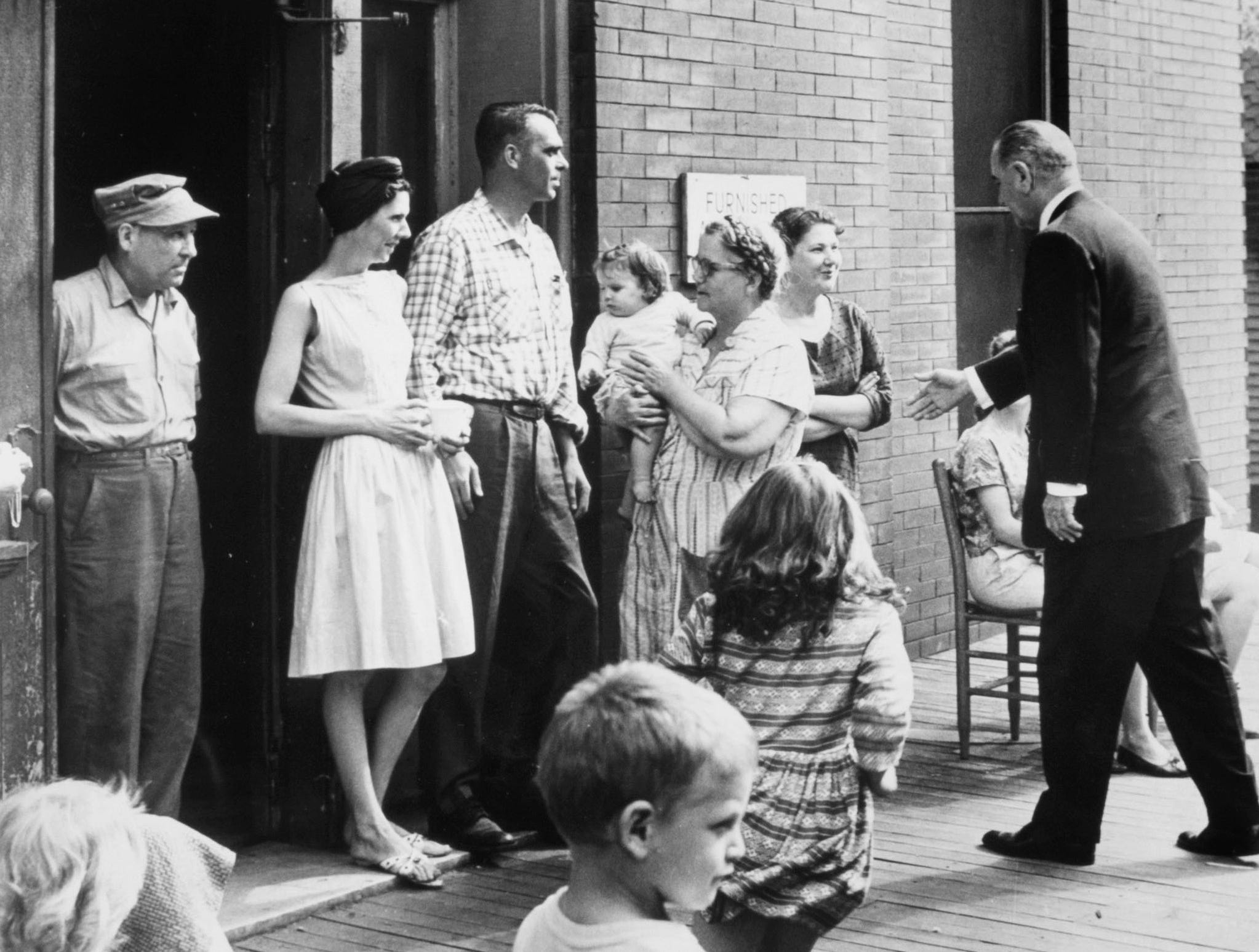 In a May 8, 1964 photograph, President Lyndon B. Johnson meets residents at an apartment house on Riverside Drive. Those pictured include Grover Helmboldt, left, Zelma Lawson with her granddaughter, Susan Anne Lawson, and Vivian Turner.
