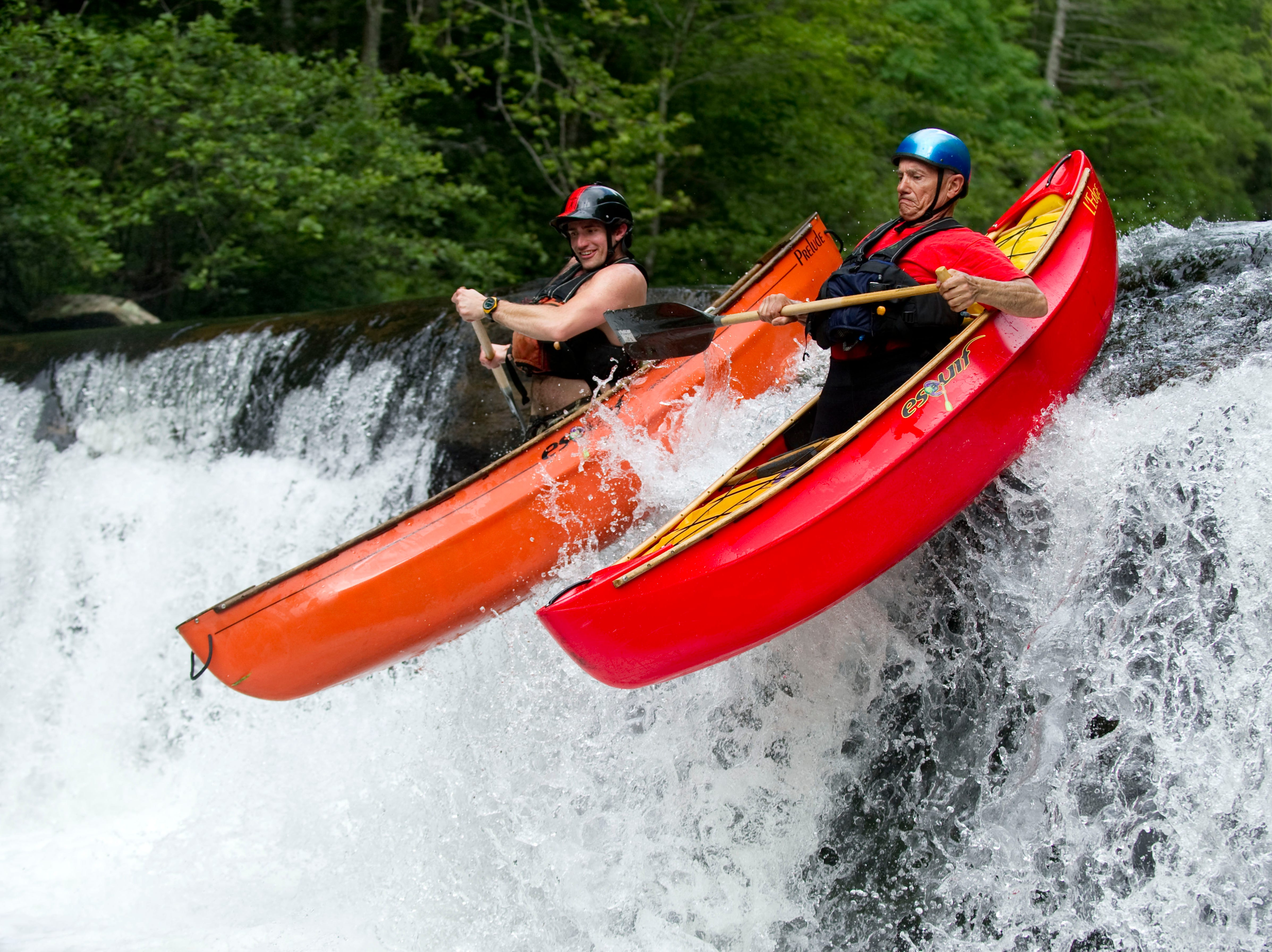 Charlie Tombras, CEO of The Tombras Group, right, and his son Dooley Tombras canoe down an 8 ft. high waterfall on the Tellico River on Sunday, June 10, 2012.