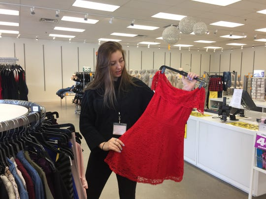 Danielle Risacher, a store manager at Charlotte Russe's outlet location at Tanger Outlets in Howell Township, shows off a dress on clearance, Monday, Feb. 18, 2019. The store is one of four Michigan stores liquidating and closing.