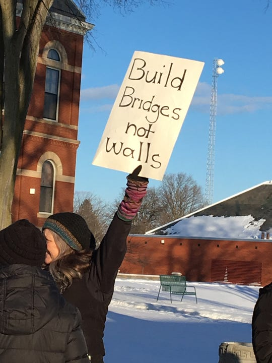 "Tyrone Township resident Laura Houston holds up a sign reading ""Build bridges not walls"" during a protest on Monday Feb. 18, 2019 outside the historic courthouse at 200 E. Grand River Avenue in Howell. Houston and others protested a national emergency declaration President Donald Trump made last week to secure money to build a wall along the U.S.-Mexico border. Similar protests occurred across the country."