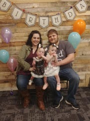 Beth and Daryl Hartzler hold their twins, Autumn and River, who celebrated their first birthday in November.