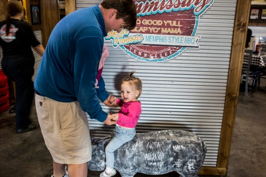 February 18, 2019 - Parker Rush helps his daughter, Eleanor, 3, balance on top of a pig while at the Collierville Commissary on Monday. The Collierville Commissary is located at 3573 S. Houston Levee Rd. in Collierville.