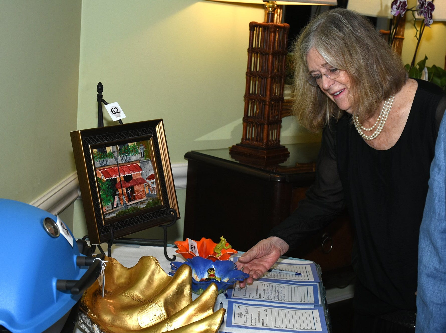 """Artist JoAnn Sanborn checks her silent auction bid. The Marco Island Cdenter for the Arts held """"Celebrate Art by the Sea,"""" their annual gala, Saturday evening at the Island Country Club."""