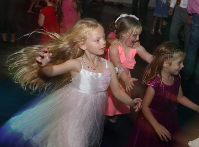 Girls swirl as they enjoy a conga line at the dance.