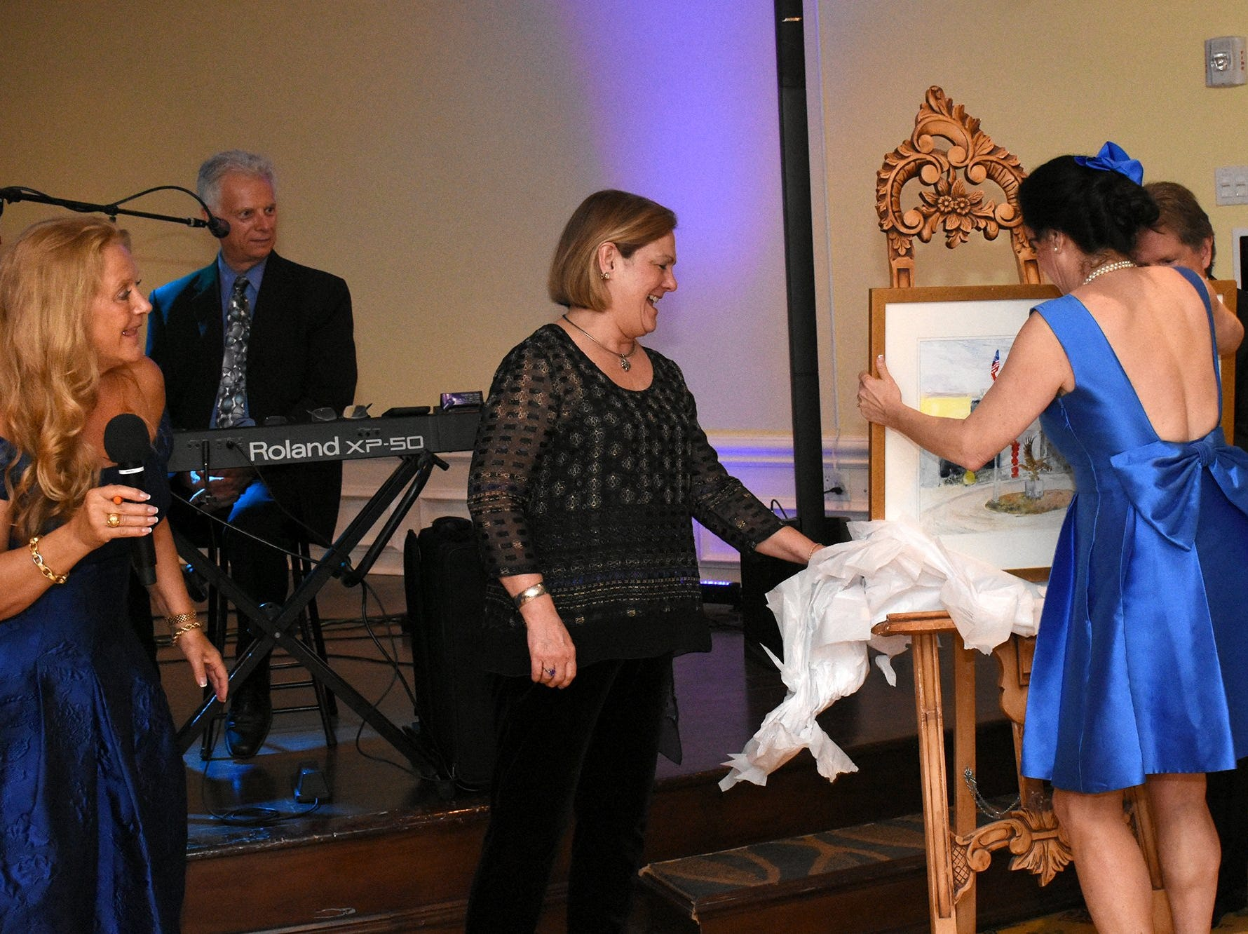 """Gala chair Kim Porter, left, watches as executive director Hyla Crane unwraps her gift painting, created by Nancy Falciani, center. The Marco Island Cdenter for the Arts held """"Celebrate Art by the Sea,"""" their annual gala, Saturday evening at the Island Country Club."""