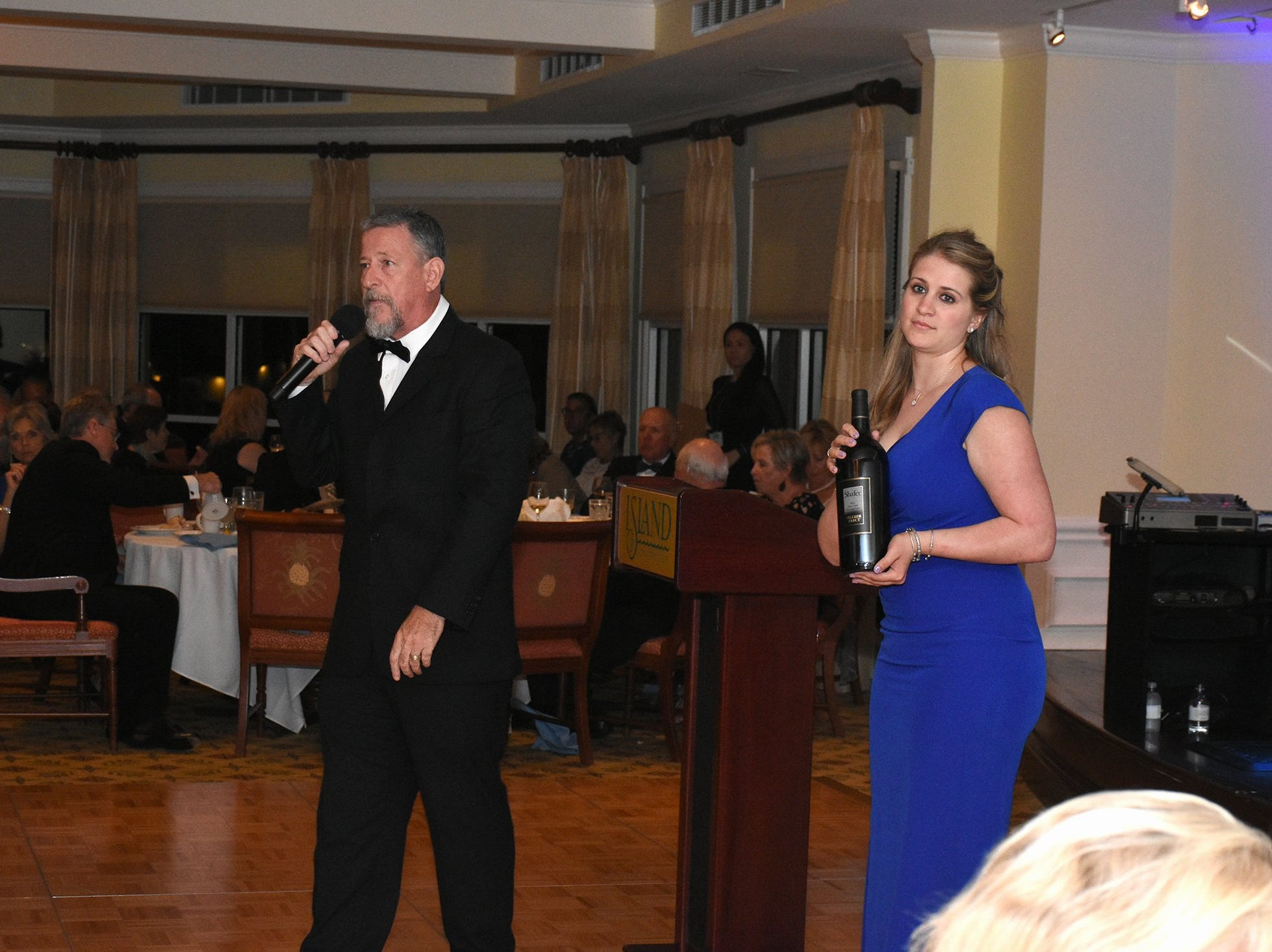 """Auctioneer Kevin Benson sells a bottle of pricey wine shown by Kim Porter's daughter Caroline. The Marco Island Cdenter for the Arts held """"Celebrate Art by the Sea,"""" their annual gala, Saturday evening at the Island Country Club."""