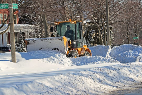 A City of Milwaukee contractor piled snow ever higher, as he widened the street next to the median at East Newberry Boulevard and North Shepard Avenue in Milwaukee on Monday.