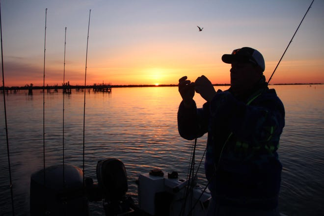 An angler prepares for a day of fishing along the Milwaukee shore of Lake Michigan.