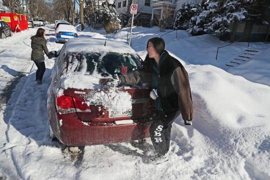 East side residents Elorine Klockow (left) and Jenai Ellner once again clear off their car in the 3200 block of North Bartlett Avenue in Milwaukee on Monday.