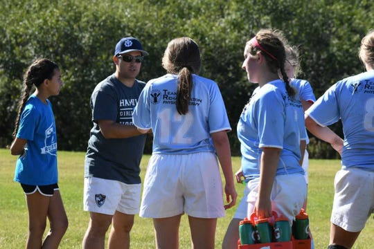 Victor Drover (wearing hat), an assistant head coach for the Hamilton High School girls' rugby team, is going to England to learn about coaching from professional rugby teams thanks to a scholarship he won.