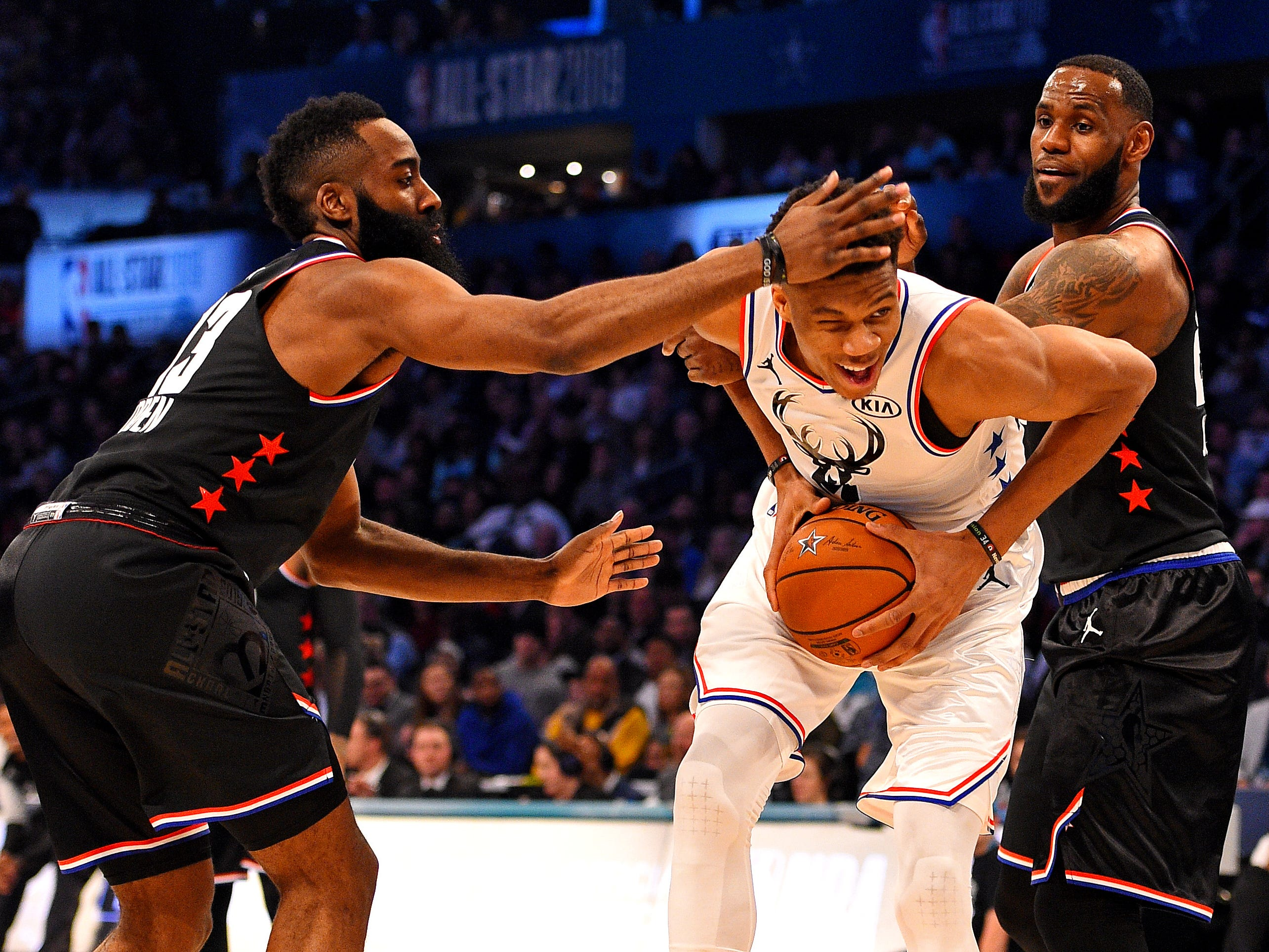 Giannis Antetokounmpo tries to split the defense of  James Harden and LeBron James on Sunday night.