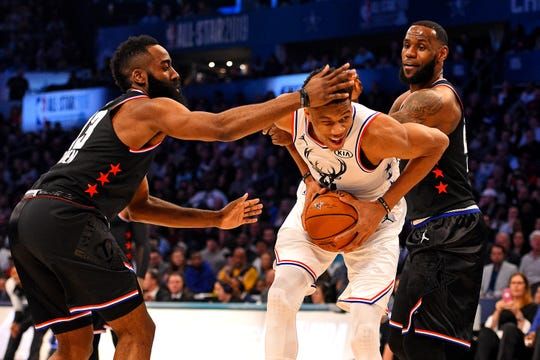 Giannis Antetokounmpo tries to split the defense of James Harden and LeBron James in the 2019 NBA all-star game.